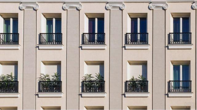Бежевый фасад многоэтажного дома с балконами украшенный купюрами классических колонн