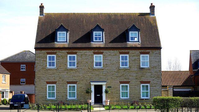 Кирпичный фасад частного дома с мансардой под черепичной крышей