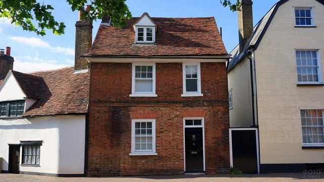 Кирпичный фасад двухэтажного домика с мансардой