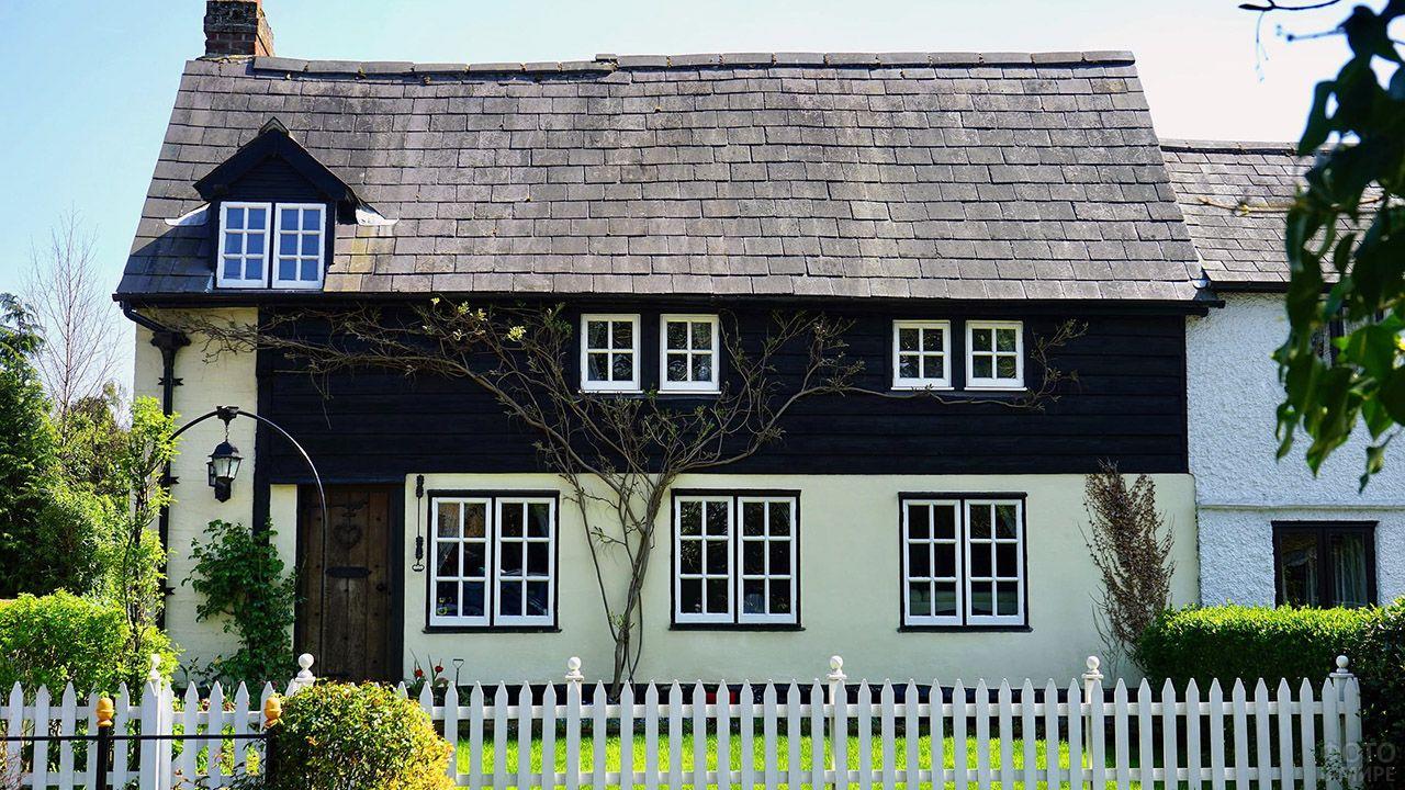 Контрастный чёрно-белый фасад сельского дома под черепичной крышей
