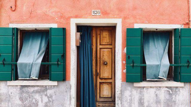 Оранжевый фасад южного домика с изумрудно-зелёными ставнями