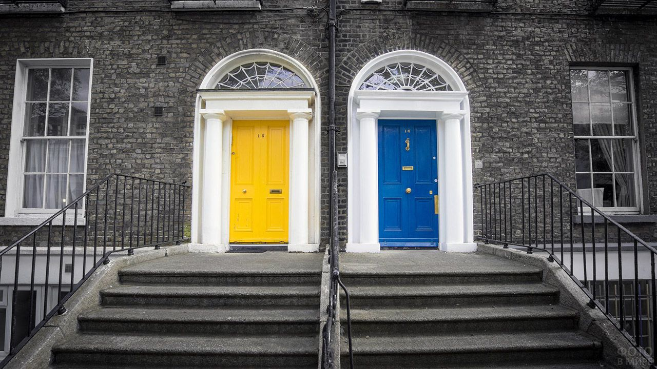 Жёлтая и синяя двери на кирпичном фасаде дублинского таунхауса