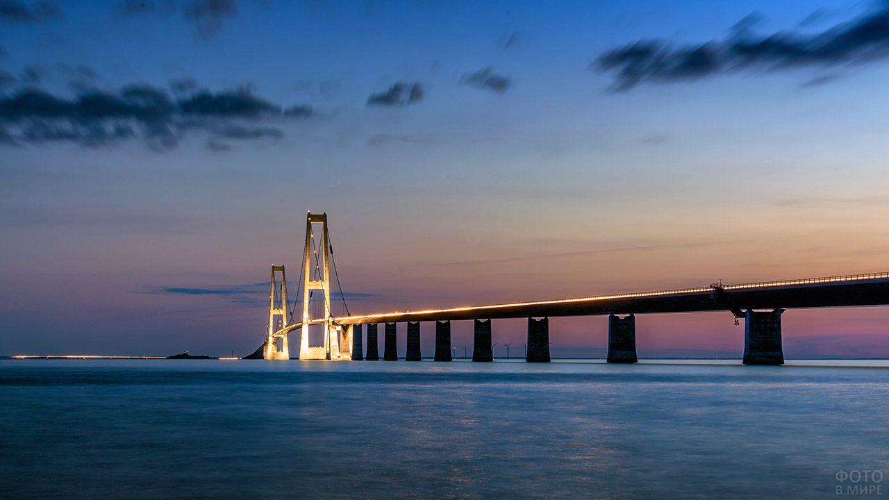 Восхитительный морской пейзаж со светящимся в ночи подвесным мостом Большой Бельт