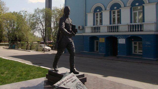 Памятник фронтовому почтальону на фоне голубого фасада здания в Воронеже