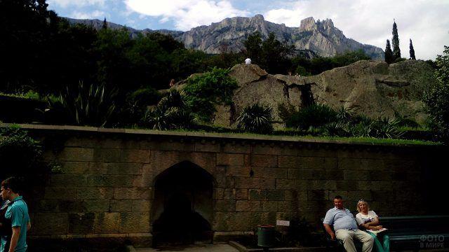 Туристы отдыхают на курортной улочке на фоне гор Крыма