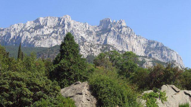 Зелёный холм и голубое небо на фоне горы Ай-Петри