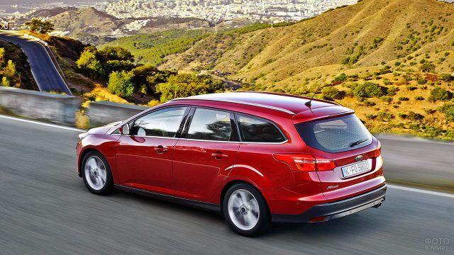 Бордовый пятидверный Форд Фокус мчится по горной дороге на фоне приморского города
