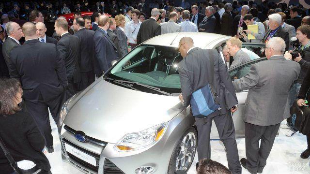 Люди на стенде автосалона разглядывают Форд Фокус 3