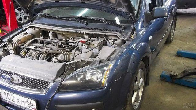 Синий Форд Фокус с поднятым капотом в автосервисе