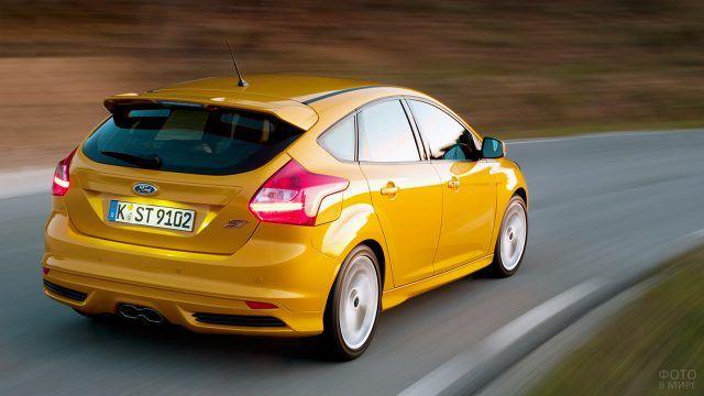 Жёлтый спорткар Форд Фокус ST мчится по трассе