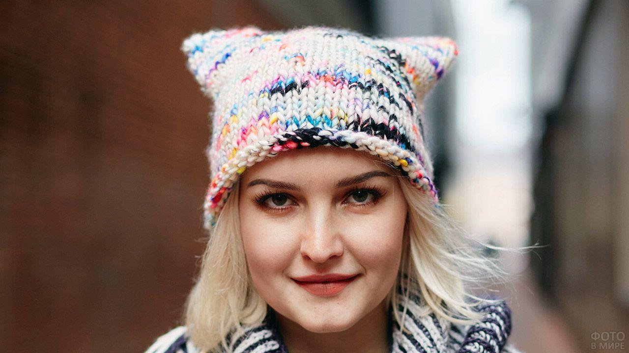 Блондинка в пёстрой шапке с кошачьими ушками