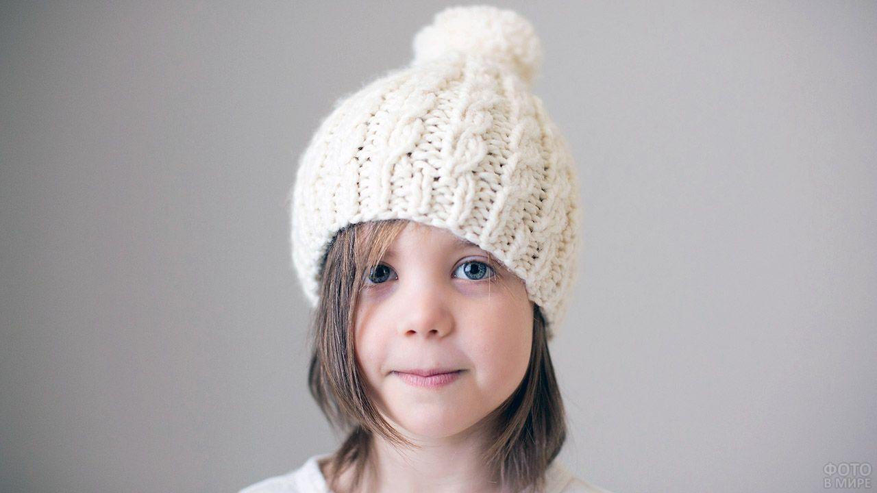 Девочка в белой лыжной шапочке домашней вязки