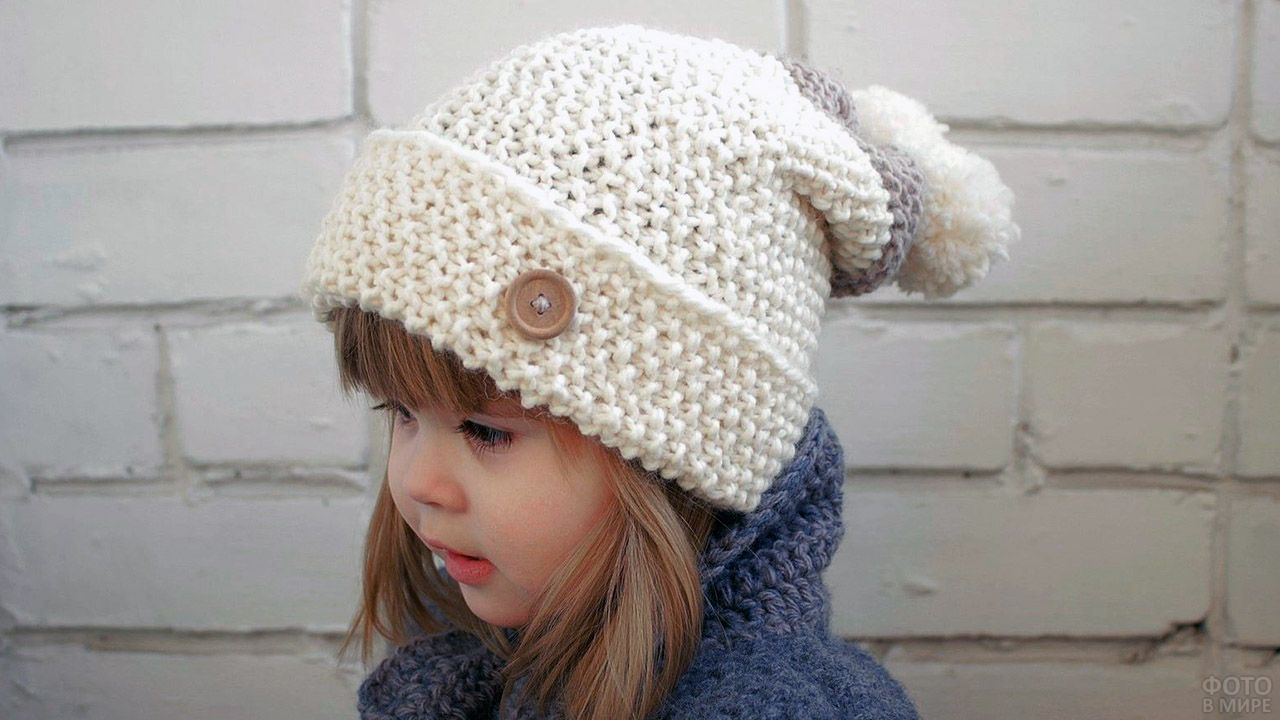 Малышка в белой лыжной шапке связанной своими руками
