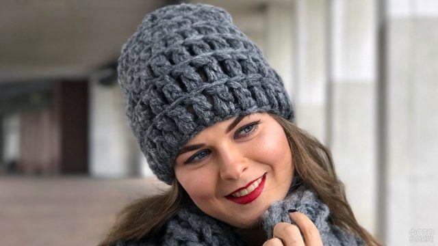 Тёмно-серая шапка-бини крупной вязки на девушке в шарфе