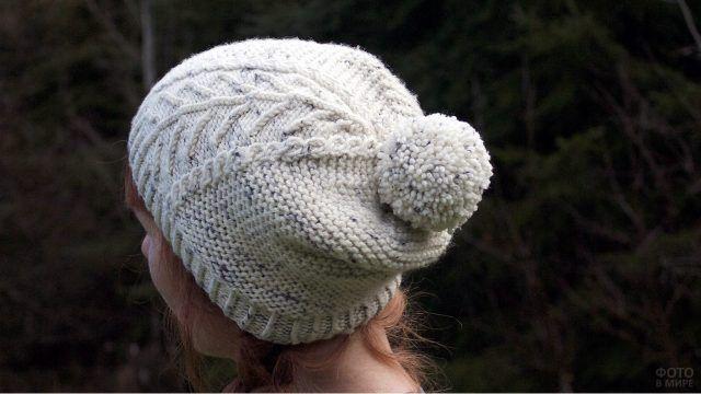 Вид девушки с затылка в белой лыжной шапочке