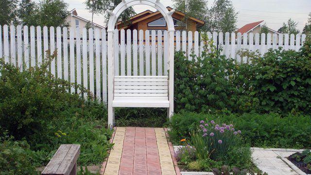 Белая скамейка в зелёном саду