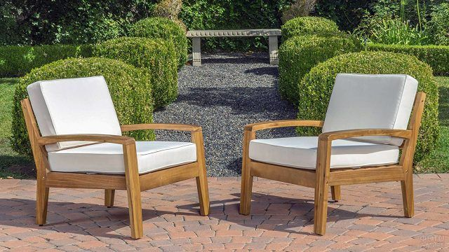 Белые глубокие кресла в саду
