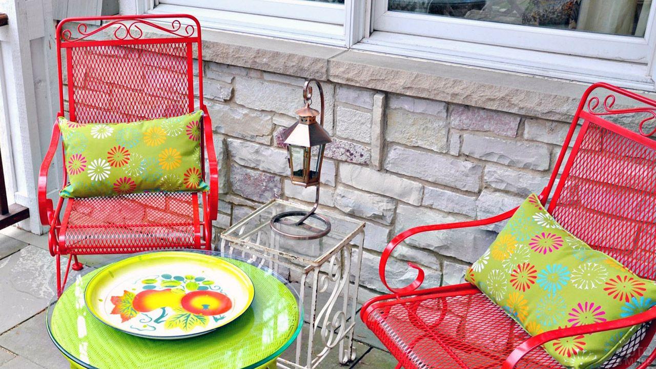 Красочная металлическая мебель с пёстрыми подушками