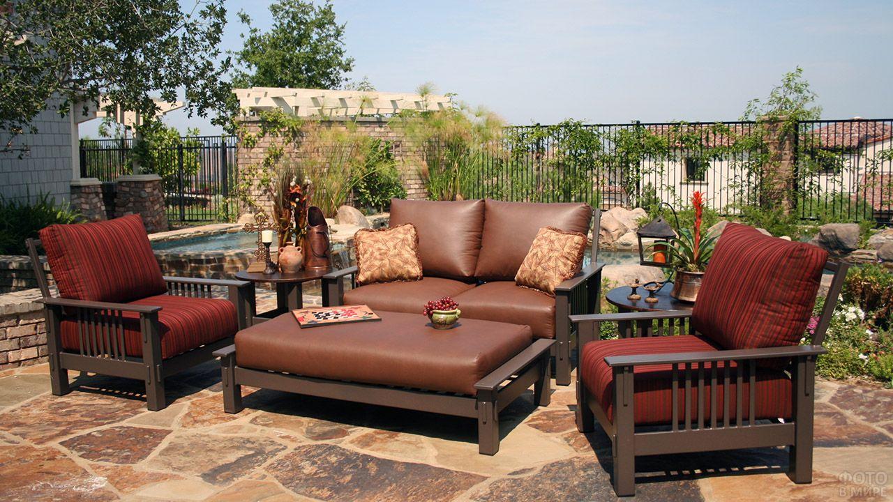 Открытая терраса с классическим кожаным диваном и бархатными креслами