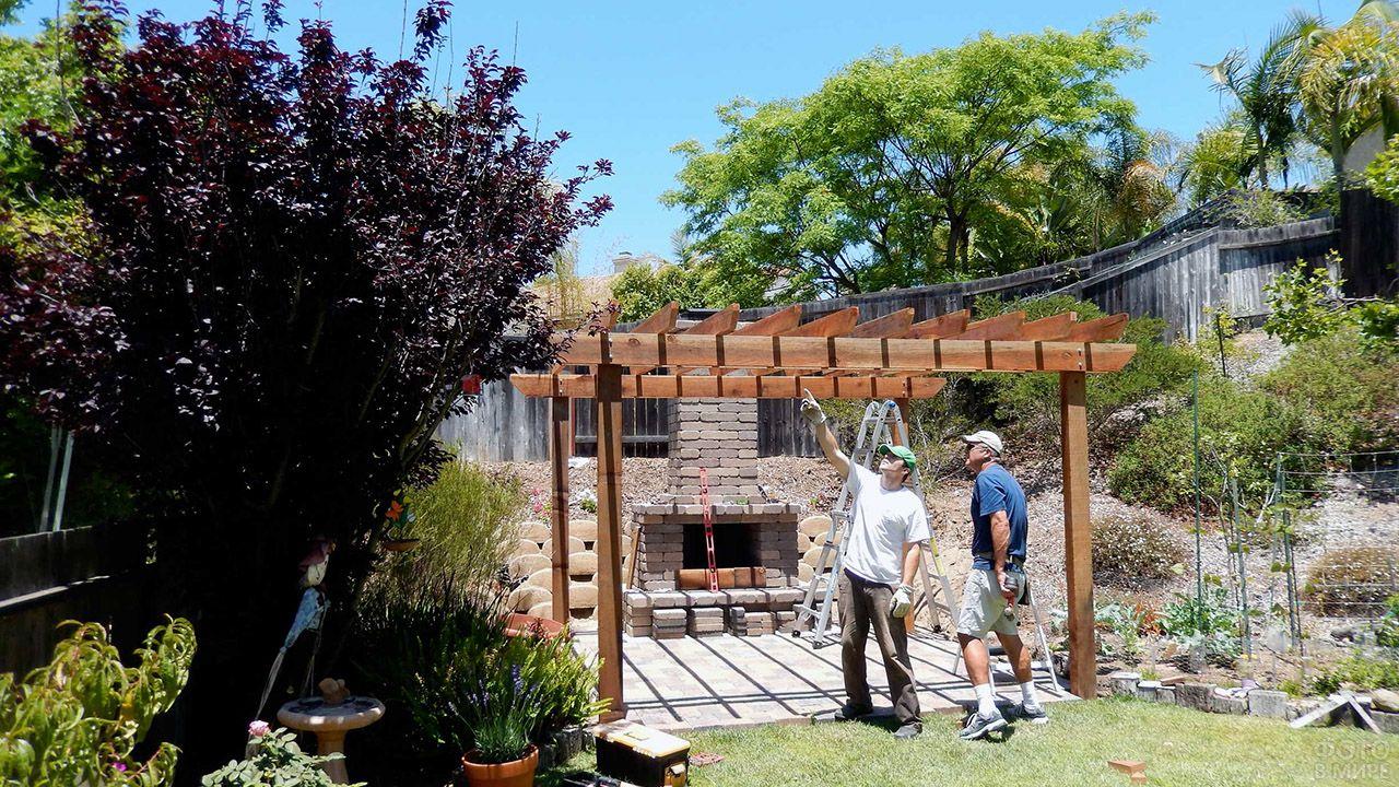 Рабочие устанавливают перголу в саду