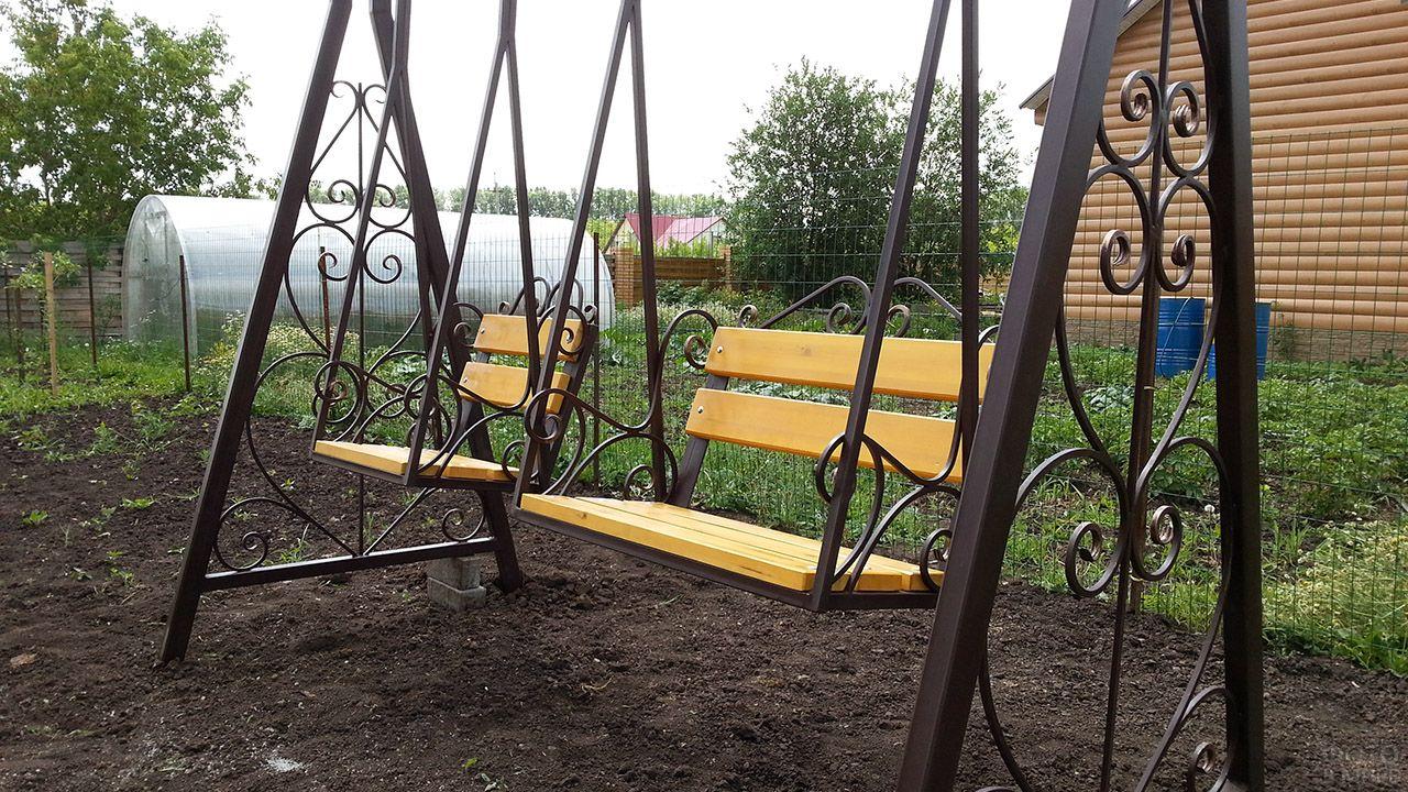 Деревянные сиденья кованных ажурных качелей