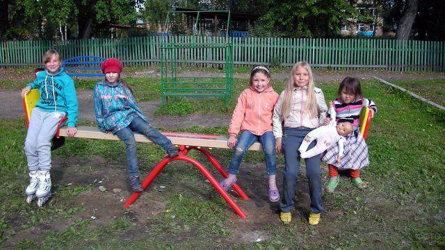 Дети во дворое на качелях-балансир
