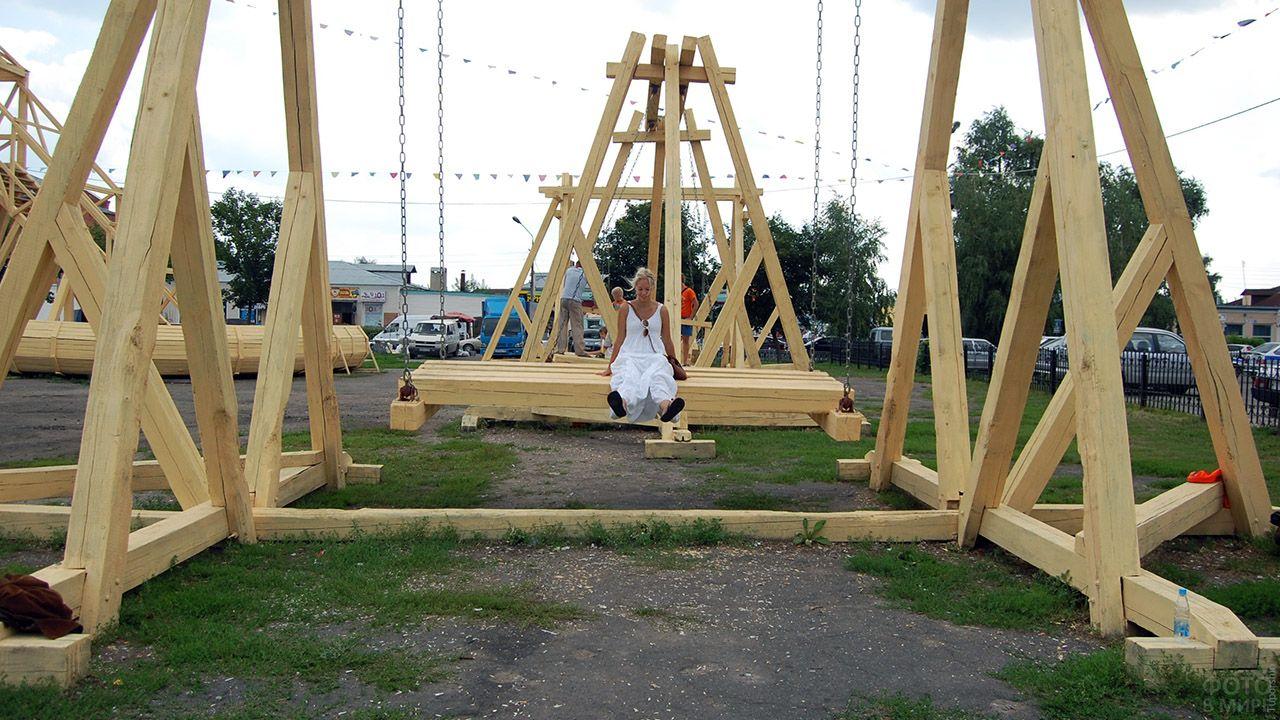 Девушка на гигантских деревянных качелях