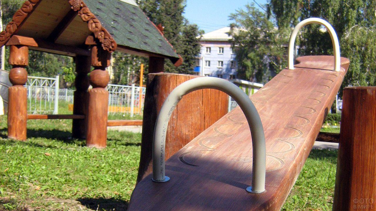 Фрагмент детской площадки из брёвен с качелями