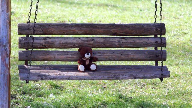 Игрушечный медвежонок на садовых качелях