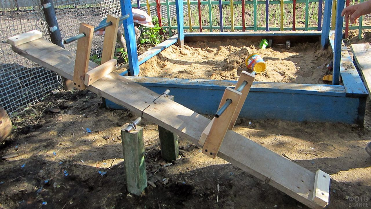 Маленькие качели-балансир рядом с песочницей