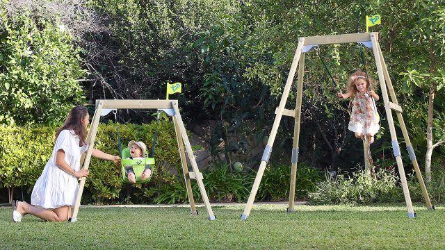 Малыши с мамой на деревянных качелях в саду