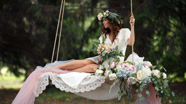 Невеста на нарядных качелях с текстилем и цветами