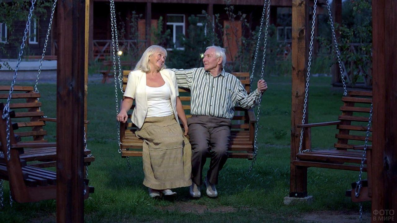 Пожилая счастливая пара на садовых качелях летним вечером