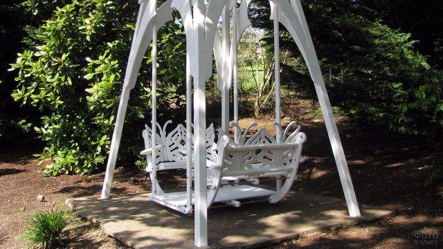 Резные белые качели в саду