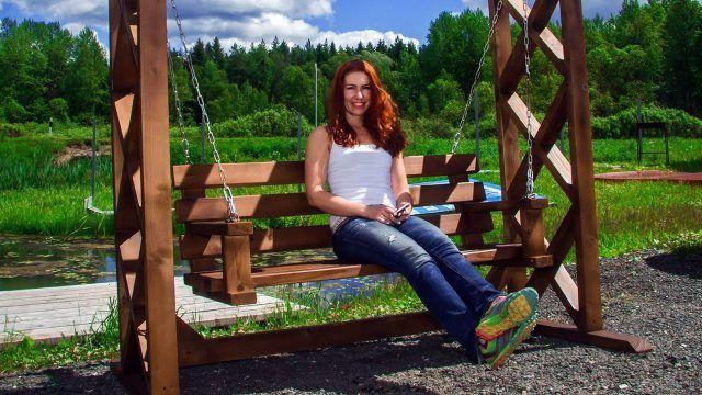 Рыжая девушка на деревянных качелях у пруда