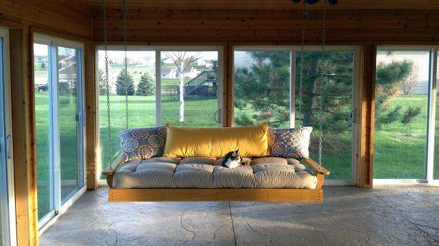 Застеклённая веранда с диваном-качелями