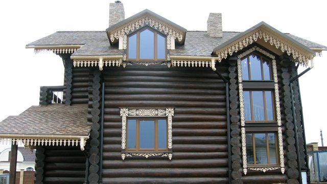 Резные карнизы на тёмном фасаде деревянного дома