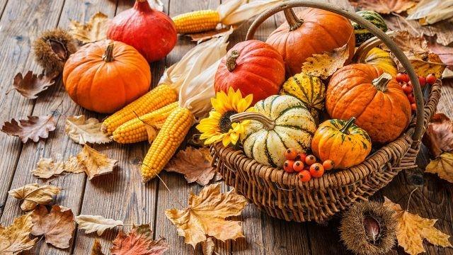 Овощи в корзинке и на деревянном столе с осенними листьями