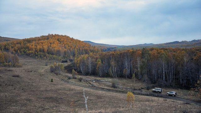 Два джипа едут через осенний лес в уральских горах к вершине Иремель