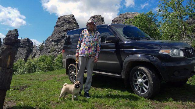 Туристк с собакой на фоне УАЗ Патриот на горе Колпаки