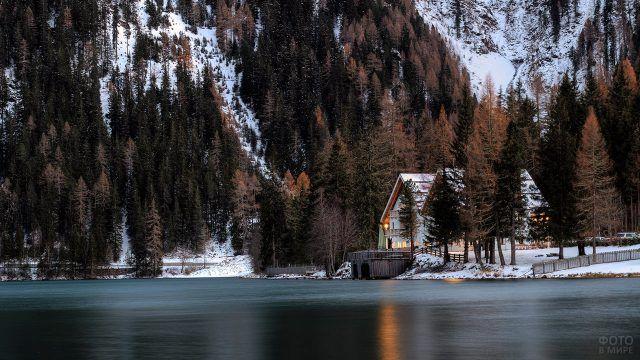 Белый двухэтажный дом под высокими елями на берегу горного озера зимой