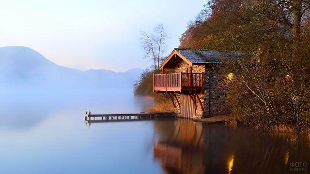 Дом из камня на берегу озера с пирсом и воротами для лодки