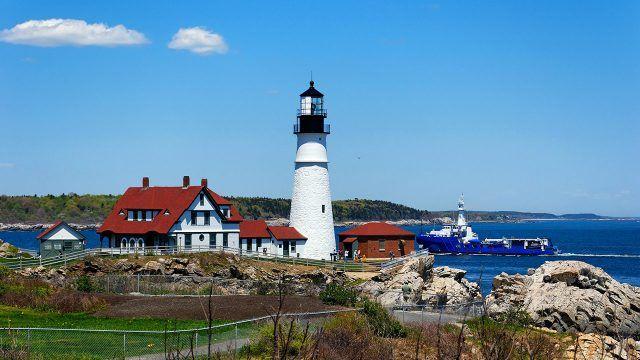 Дом с маяком на каменистом берегу и синий корабль в море