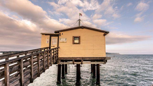 Дощатый домик на сваях в море