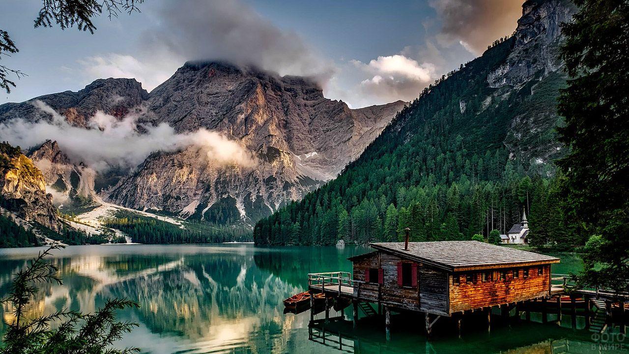 Дощатый домик на сваях в воде горного озера