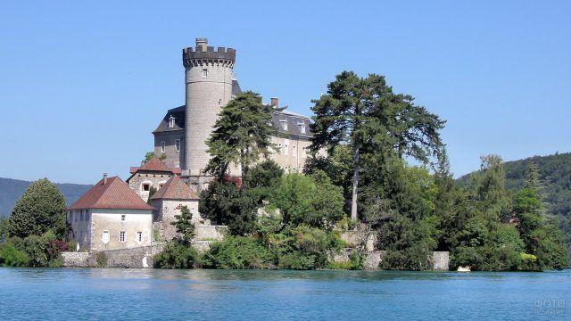 Французский замок средневековья среди деревьев на берегу