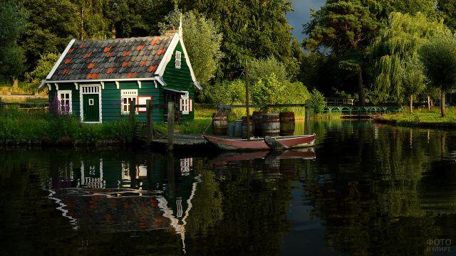 Маленький зелёный домик на берегу и лодка