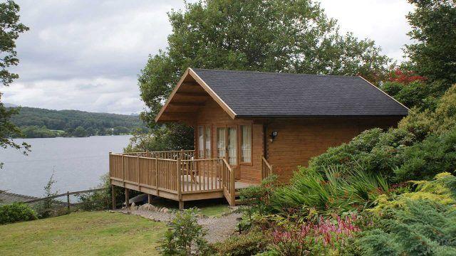 Небольшой скандинавский бревенчатый домик с цветущим садом на берегу озера