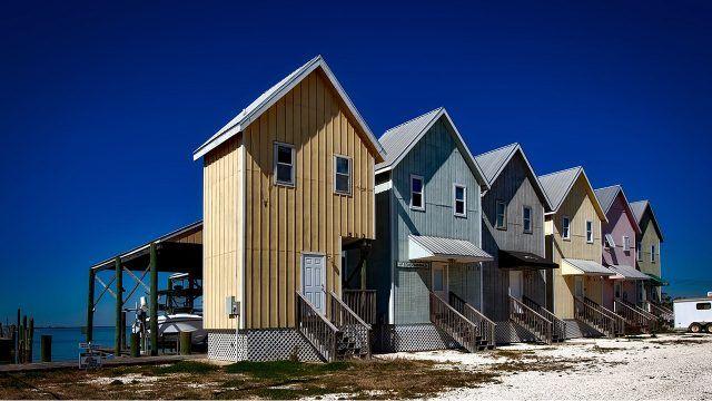 Разноцветные курортные домики у моря с навесами для лодок