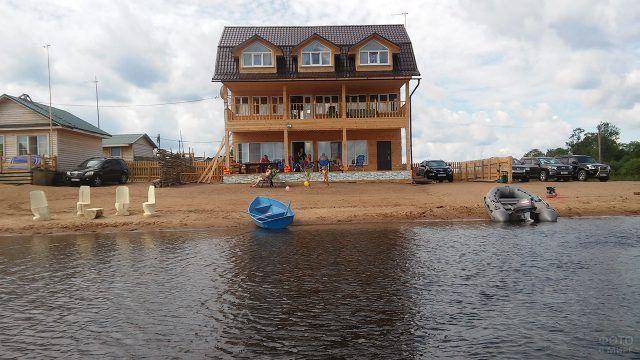 Семья на веранде большого дома на берегу реки с лодками